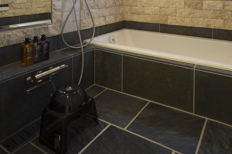 浴室:天然石の壁・床とホーロー浴槽